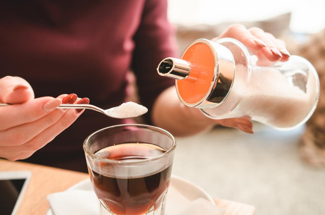 woman-pouring-sugar-into-hot-drink